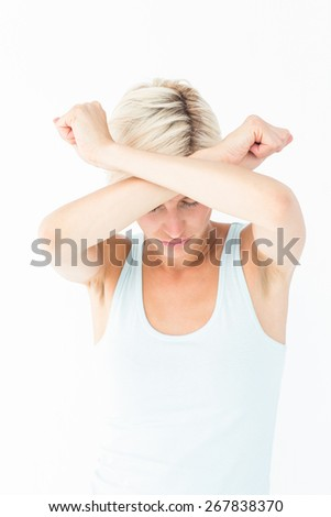 Upset woman holding her arms in front of her headon white background