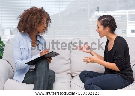 Upset woman speaking to her therapist while she is taking notes