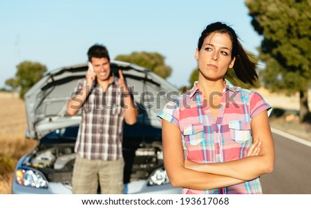 Upset woman waiting for car help while man arguing on the cellphone with insurance service. Couple in road trip problems because of breakdown engine. - stock photo