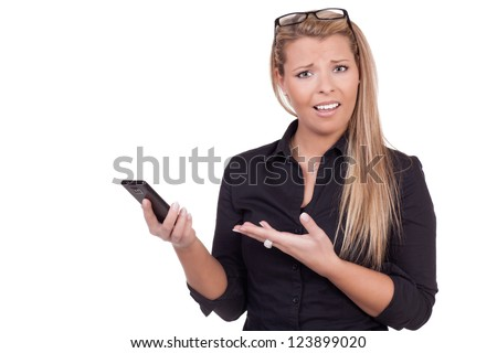 Upset woman with a confused expression frowning and pointing at her mobile or smartphone which she is holding in the other hand upper body studio portrait isolated on white - stock photo