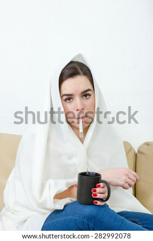 Upset woman with thermometer in her mouth sick colds, flu, fever and migraine in bed with black cup of tea or coffee. Girl with virus. Female model caught cold covered with white blanket at home. - stock photo