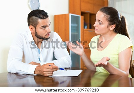 Upset worried  male and female sitting with business papers