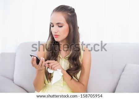 Upset young brunette holding mobile phone and tissue in bright living room