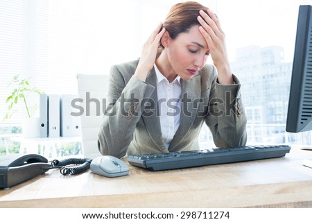 Upset young business woman sitting with head in hands in front of computer at office desk - stock photo