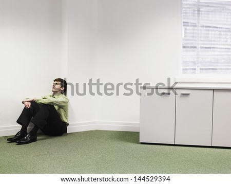 Upset young businessman sitting on floor in the corner at office - stock photo