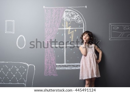 Upset young child in her imaginary room depicted on the grey background with chalk. Little girl stands near the window. Kid is disappointed to stay home during bad weather. - stock photo