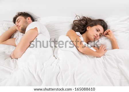 Upset young couple having disagreement lying side by side in bed facing in opposite directions - stock photo
