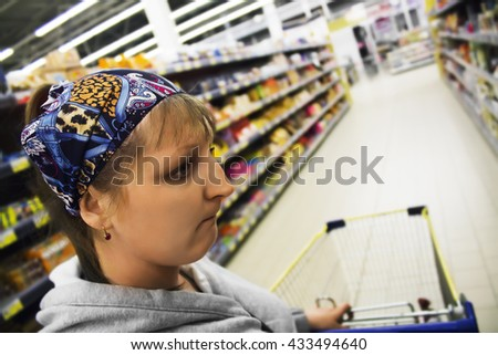 Upset young girl at the grocery store chooses a product. Cart at the grocery store. The woman in the supermarket with an empty trolley. Sad girl in the shop. Small selection of goods and big prices.  - stock photo