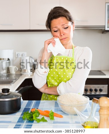 Upset young housewife cooking dinner for her family
