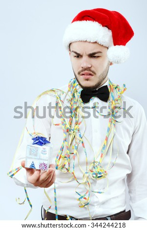 Upset young man, wearing in white shirt and santa hat, looking on present in his hand, on white background, in studio, waist up - stock photo
