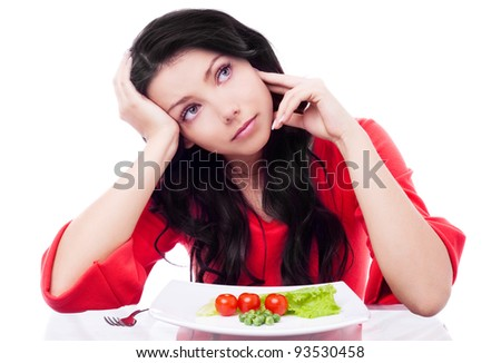 upset young woman keeping a diet and eating vegetables in the kitchen at home