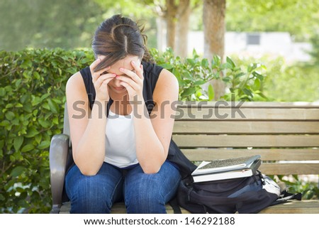 Upset Young Woman Sitting Alone with Her Head in Her Hands on Bench Next to Books and Backpack. - stock photo