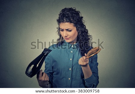 Upset young woman with hair dryer and hair brush   - stock photo
