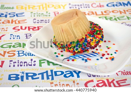 upside down birthday cupcake with colorful sprinkles and candle on white square plate - stock photo