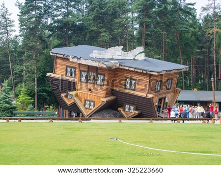 Upside Down House in Szymbark Poland. It stands on its roof and visitors walk on the ceilings and it is decorated in the socialist style of the 1970s. - stock photo