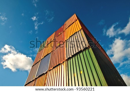 Upside view of a staple of cargo container against a blue sky with clouds - stock photo