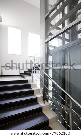 Upstairs and elevator in modern offices building - stock photo