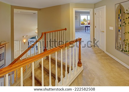 Upstairs hallway with staircase. Staircase with carpet steps, white railings with brown trim - stock photo