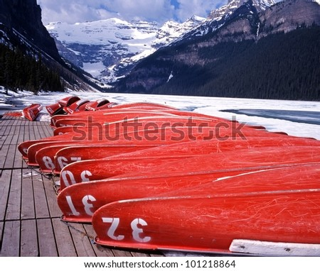 Upturned canoes on the edge of Lake Louise with snow capped mountains to the rear, Banff National Park, Alberta, Canada. - stock photo