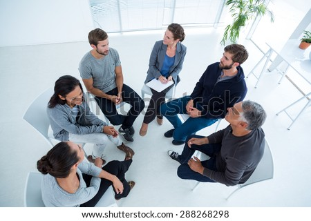 Upward angle view of a therapy group in session sitting in a circle in a bright room - stock photo