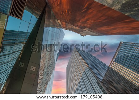 Upward fish eye view of tall skyscrapers against a blue sky in the downtown business area. - stock photo
