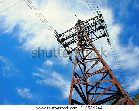 Upward view diagonally to the power line and pylon against a blue sky with white clouds - stock photo
