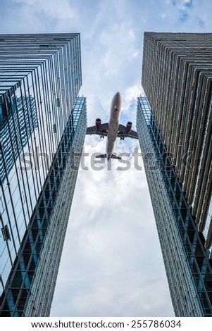 upward view of the airplane between the two glass skyscrapers - stock photo
