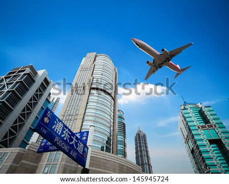 upward view of the airplane with modern financial buildings in shanghai - stock photo