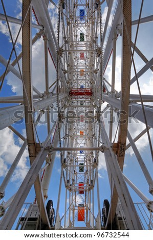 Upward view of the intricate mechanical innards of a carnival ferris wheel against a blue cloudy sky. This is a HDR image.