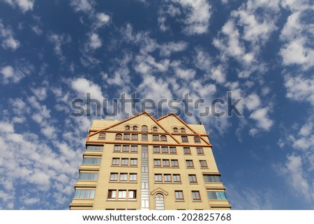 Upward view on modern luxury apartment against cloudy blue sky with empty space at the top for your text - stock photo