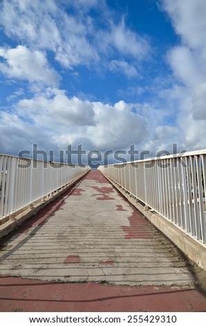 Upwards a dirty concrete footbridge with white fence - stock photo