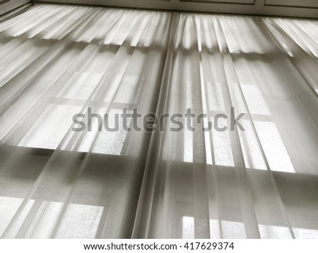 Upwards view of a line curtain covering a tall window - stock photo