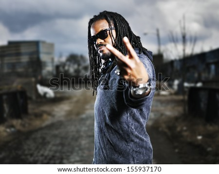 urban african man showing peace sign. - stock photo