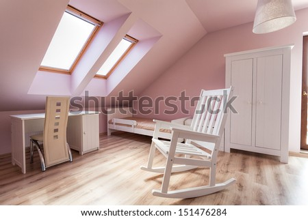 Urban apartment - bright girls room with rocking chair - stock photo