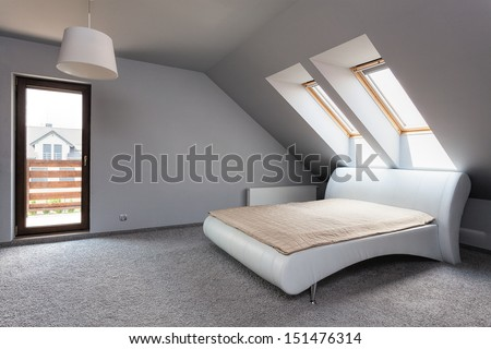 Urban apartment - grey bedroom with comfortable bed - stock photo