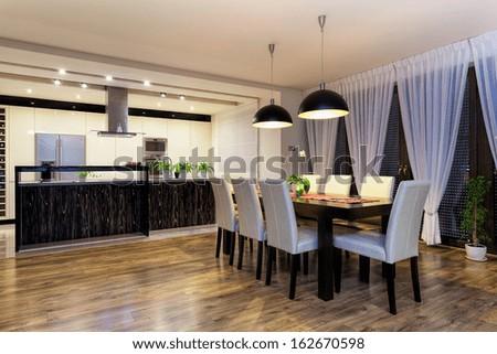 Urban apartment - Spacious kitchen with wooden black table - stock photo