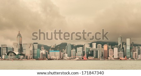 Urban architecture in Hong Kong Victoria Harbor with city skyline and cloud in the day with yellow tone. - stock photo