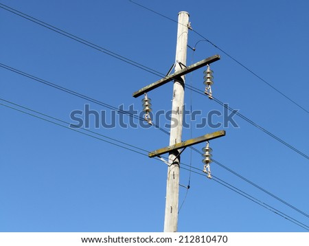urban area power lines in dark blue sky close up for electricity network and technology improving  - stock photo