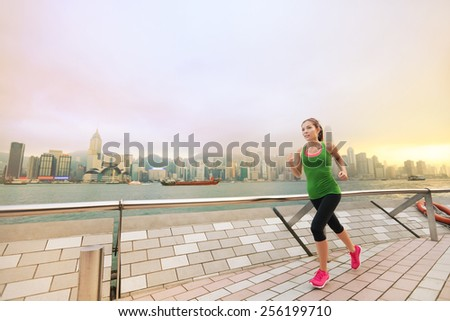 Urban Asian Chinese woman jogging in Hong Kong city. Female fitness athlete running training living healthy lifestyle on Tsim Sha Tsui Promenade and Avenue of Stars in Victoria Harbour, Kowloon. - stock photo