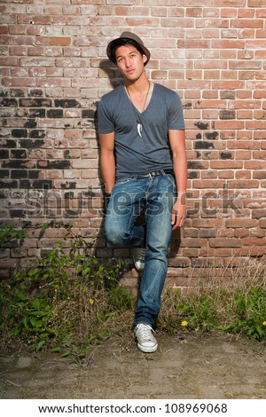 Urban asian man. Good looking. Cool guy. Wearing grey shirt and hat and jeans. Standing in front of brick wall. - stock photo