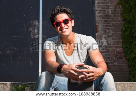 Urban asian man with red sunglasses and skateboard sitting on stairs. Good looking. Cool guy. Wearing grey shirt and jeans. Old neglected building in the background.