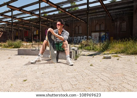 Urban asian man with red sunglasses and skateboard sitting on street. Good looking. Cool guy. Wearing blue white striped sweater and green shorts. Old neglected building in the background.