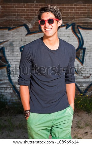 Urban asian man with red sunglasses. Good looking. Cool guy. Wearing dark blue shirt and green shorts. Standing in front of brick wall with graffiti.
