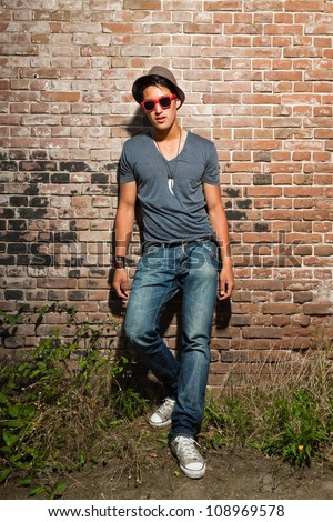 Urban asian man with red sunglasses. Good looking. Cool guy. Wearing grey shirt and hat and jeans. Standing in front of brick wall. - stock photo
