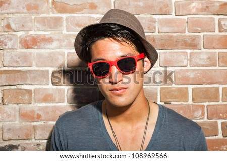 Urban asian man with red sunglasses. Good looking. Cool guy. Wearing grey shirt and hat. Standing in front of brick wall.