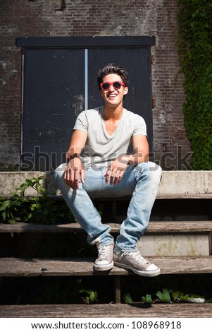 Urban asian man with red sunglasses sitting on stairs. Good looking. Cool guy. Wearing grey shirt and jeans. Old neglected building in the background. - stock photo