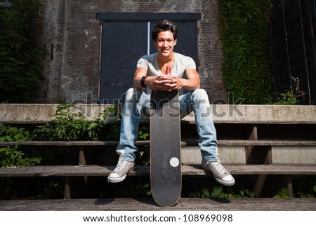 Urban asian man with skateboard sitting on stairs. Good looking. Cool guy. Wearing grey shirt and jeans. Old neglected building in the background.