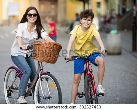 Urban biking - girl and boy riding bikes in city - stock photo