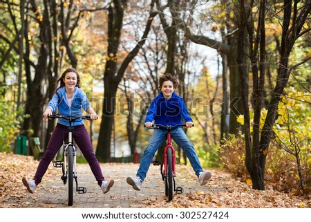 Urban biking - girl and boy riding bikes in city park  - stock photo