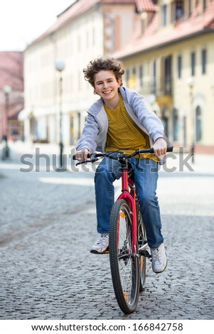 Urban biking - teenage boy and bike in city  - stock photo